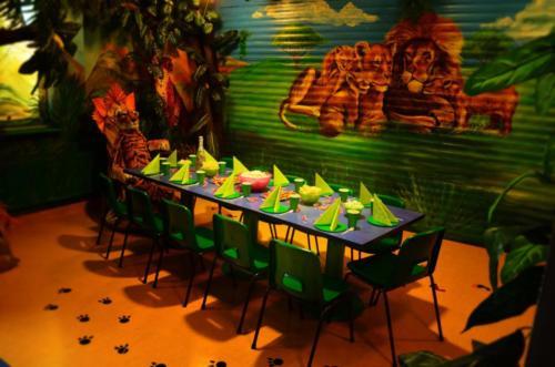 Na zdjęciu widać zastawiony stół w pokoju urodzinowym Dżungla. Stół przygotowany jest na przyjęcie urodzinowe.
