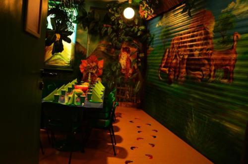 Na zdjęciu widać stół wraz z zastawą oraz dekoracje pokoju Dżungla w Centrum Zabaw Rodzinnych Family Park.