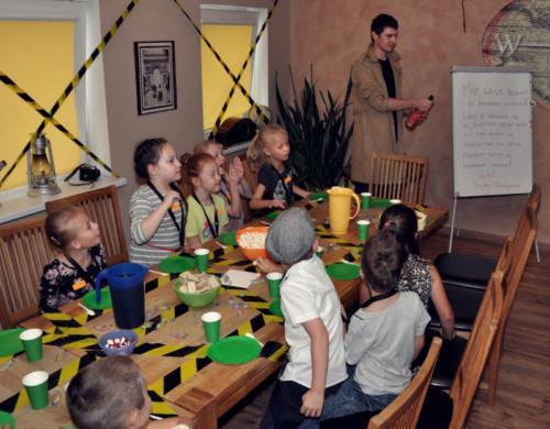Zdjęcie przedstawia dzieci podczas przyjęcia urodzinowego w pokoju Małego Detektywa. Animator otwiera szampana.