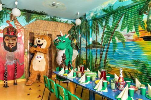 Na zdjęciu znajdują się maskotki Miś Bobuś oraz Smok Fampo w pokoju urodzinowym Dżungla.