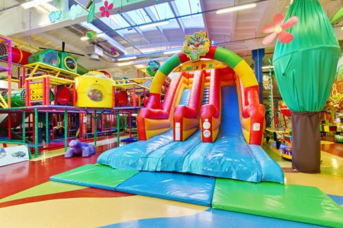 Zdjęcie ukazujące dużą, kolorową, dmuchaną zjeżdżalnię w Centrum Zabaw Rodzinnych Family Park. Obok zauważyć można fragment kolorowego labiryntu z atrakcjami - figloraju.