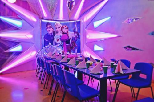 """Fotografia przedstawia wnętrze pokoju urodzinowego Kraina Lodu w Centrum Zabaw Rodzinnych Family Park. Na pierwszym planie widać zastawiony stół oraz krzesełka podczas gdy w tle zaobserwować można dekorację z ilustracją postaci z filmu """"Kraina Lodu"""""""